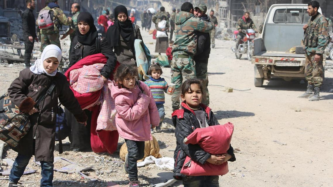 Syrian women and children walk past government soldiers as they evacuate from the town of Jisreen in the southern Eastern Ghouta, on the eastern outskirts of the capital Damascus, on March 17, 2018. (AFP)