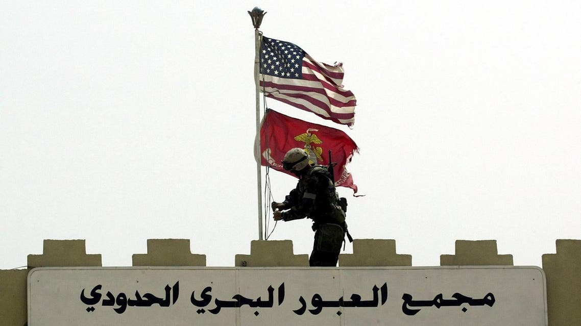 A Marine of the U.S. Marine Expeditionary Unit Fox Company 'Raiders' replaces the Iraqi flag at the entrance to Iraq's main port of Umm Qasr, with the Stars and Stripes and the flag of the Marine Corps, March 21, 2003.(Reuters)