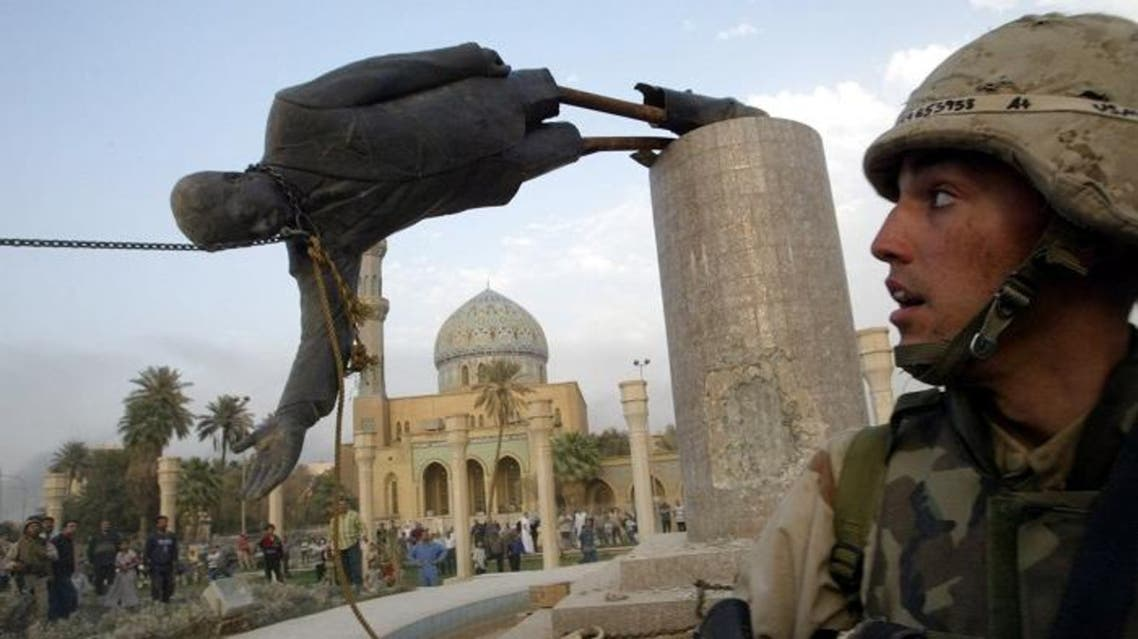 A U.S. soldier watches as a statue of Iraq's President Saddam Hussein falls in central Baghdad, April 9, 2003. (Reuters)