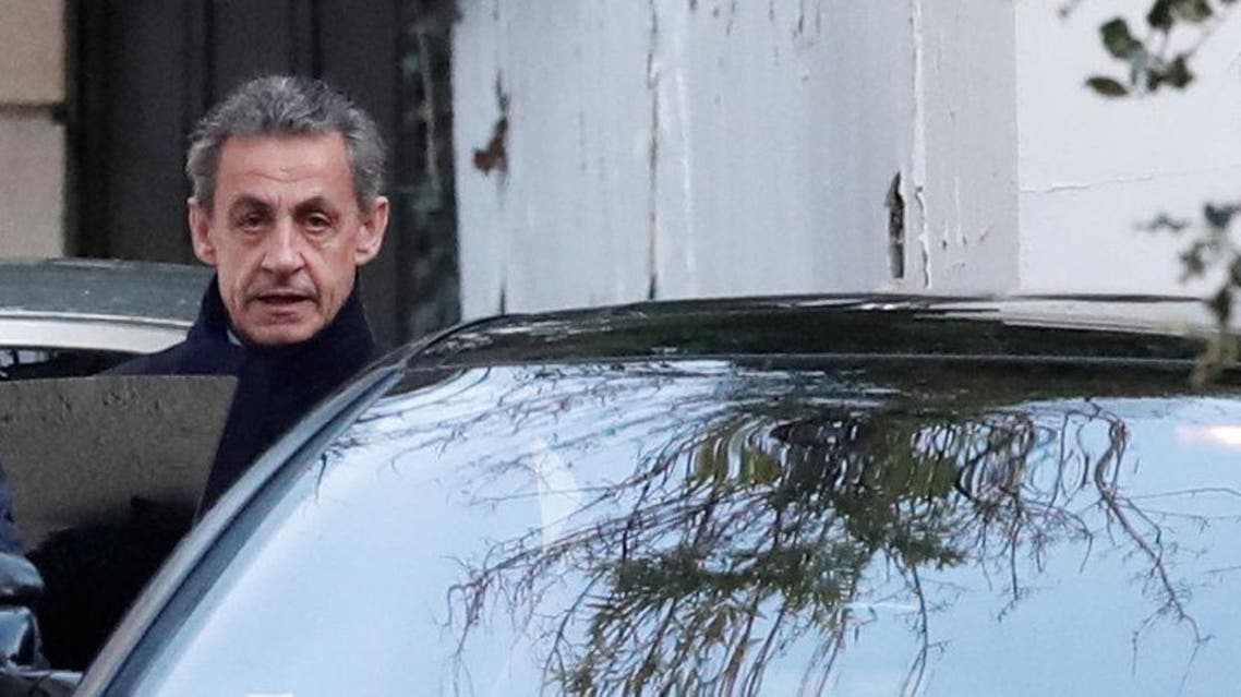 Former French President Nicolas Sarkozy enters his car as he leaves his house in Paris. (Reuters)