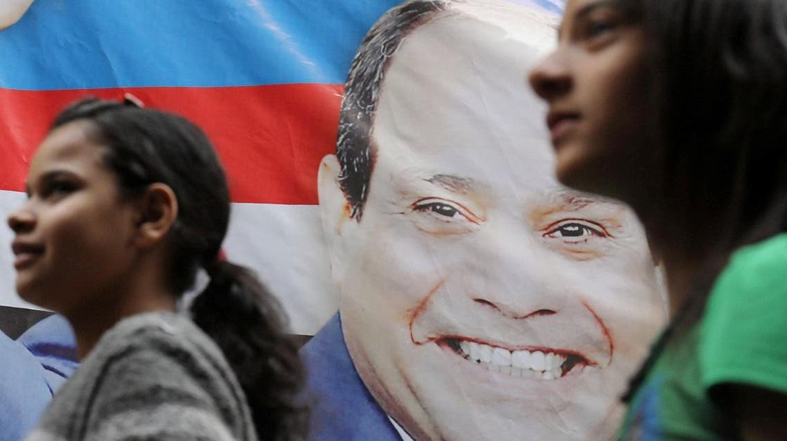 Girls walk by a poster of Egyptian President Abdel Fattah al-Sisi for the upcoming presidential election, in Cairo. (AFP)