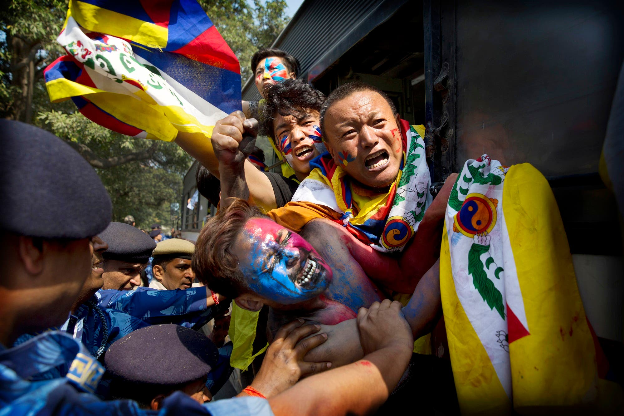 Indian para-military force soldiers push exiled Tibetan activists into a police bus during a protest outside the Chinese Embassy, in New Delhi, on March 9, 2018. (AP)