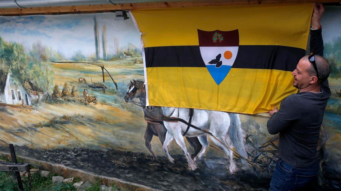 A man fixing the Liberland flag onto a wall in a private compound in Backi Monostor, Serbia, on May 1, 2015. (AP)