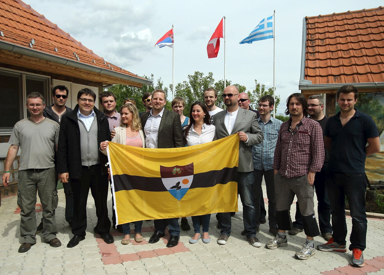 Vit Jedlicka (C) poses with the Liberland flag and future citizenships in the village of Backi Monostor, Serbia, on May 1, 2015. (Reuters)