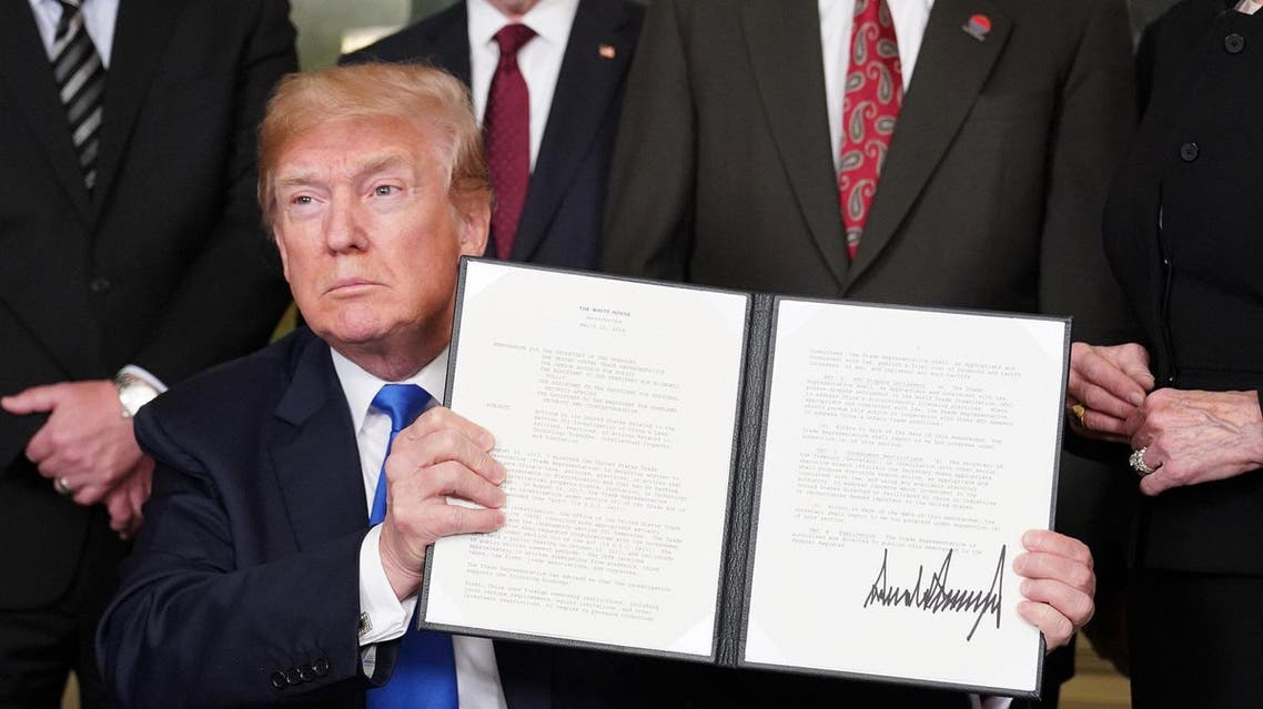 US President Donald Trump signs trade sanctions against China in the Diplomatic Reception Room of the White House in Washington, DC, on March 22, 2018.  (AFP)