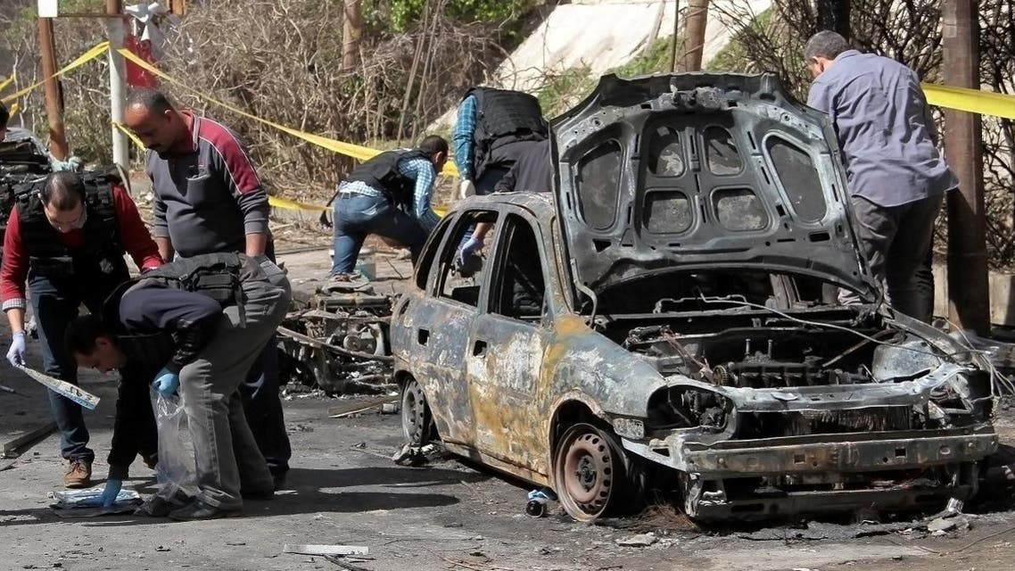 Egyptian forensics check a destroyed vehicle at the site of a bomb attack in the northern port city of Alexandria, which hit a convoy of the city's security chief, on March 24, 2018. (AFP)