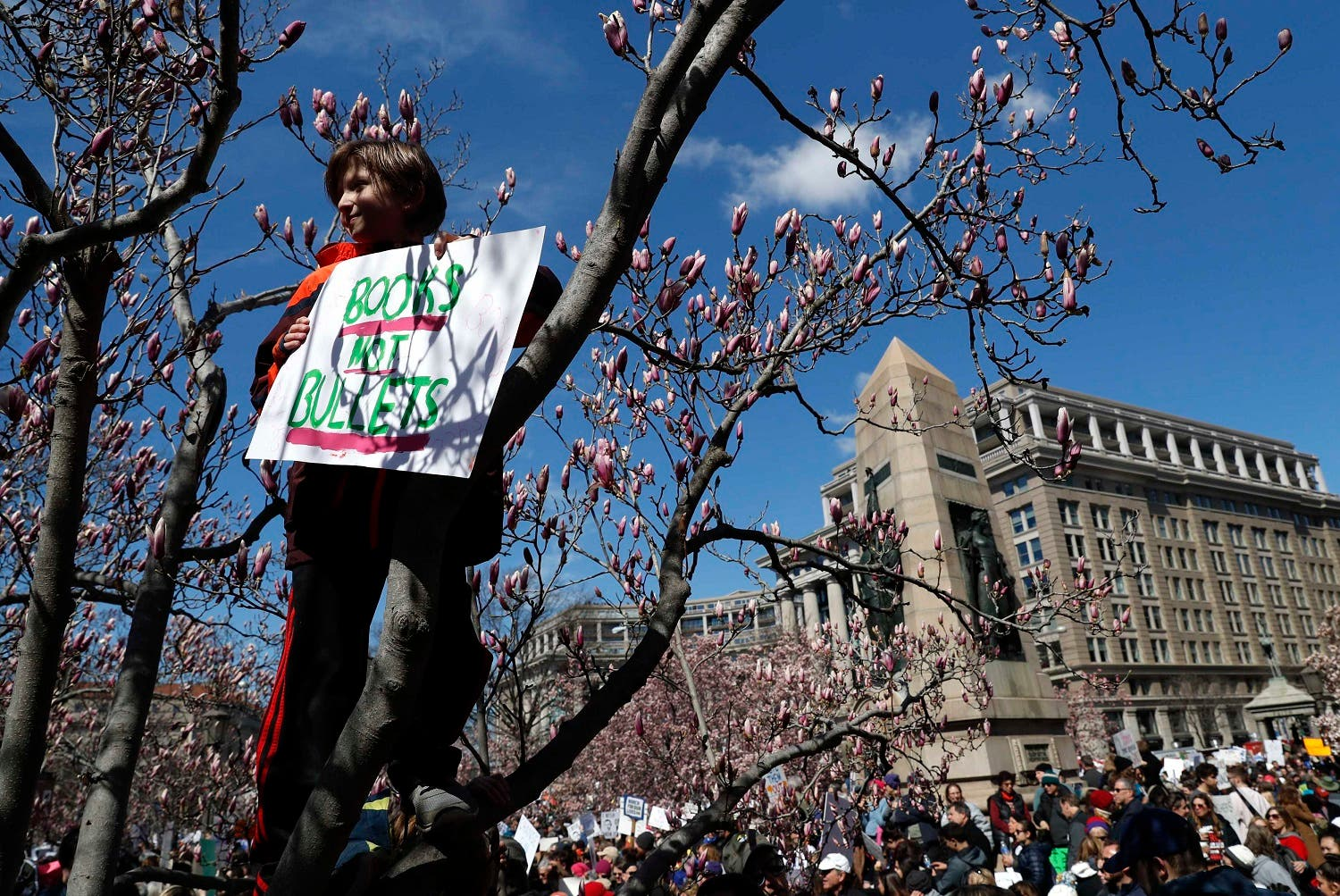 "A participant perched on a tree holds up a sign as students and gun control advocates hold ""March for Our Lives"" event at a rally in Washington, on March 24, 2018. (Reuters)"