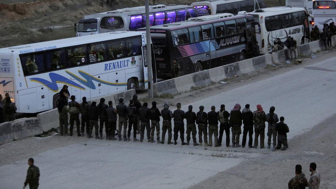 Rebel fighters pray before they are evacuated, outside Harasta in eastern Ghouta, in Damascus. (AFP)