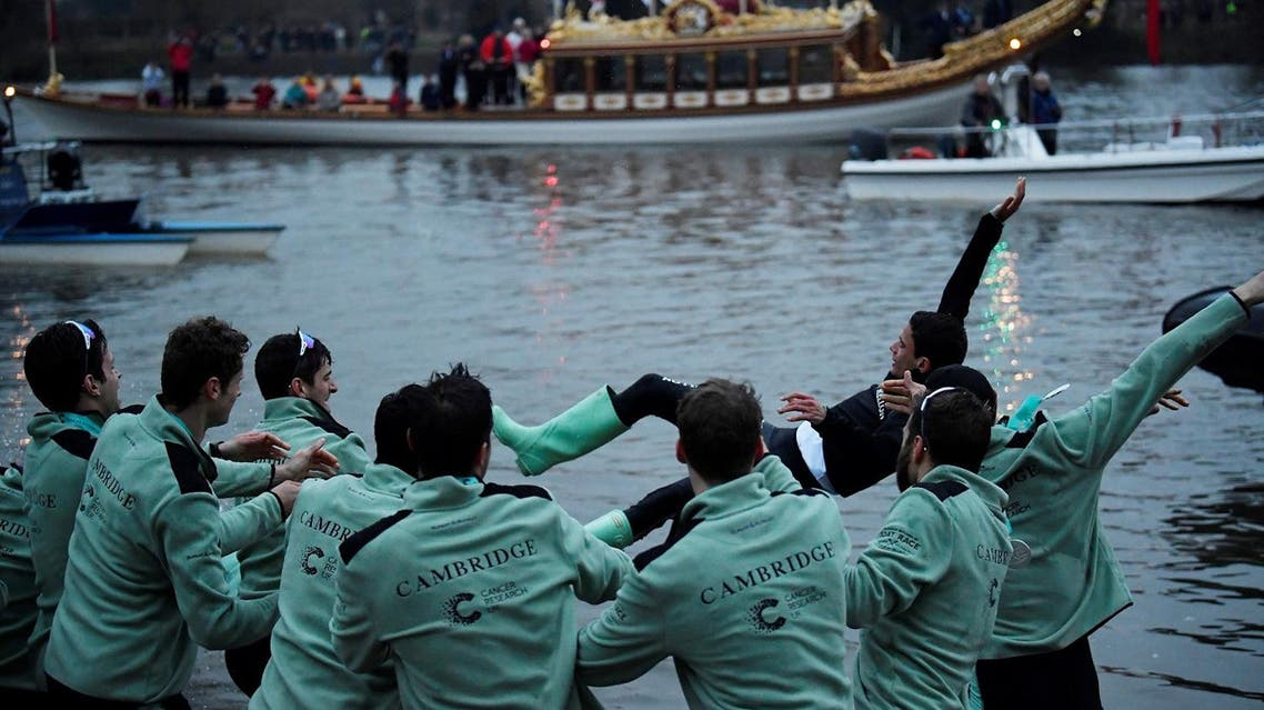 Cambridge men's Cox Hugo Ramambason is thrown into the river as they celebrate winning the boat race. (Reuters)