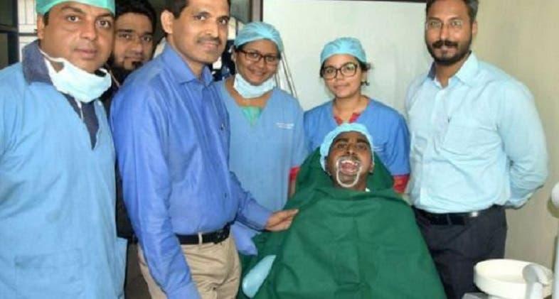 راجندرا الذي استعاد فمه، والى يمينه الجراح الذي عالجه بعملية استغرقت 4 ساعات