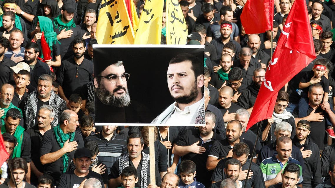 Supporters carry flags and a picture of Hassan Nasrallah and Yemen's Houthi movement leader, Abdel Malek al-Houthi, in Beirut on October 12, 2016. (Reuters)