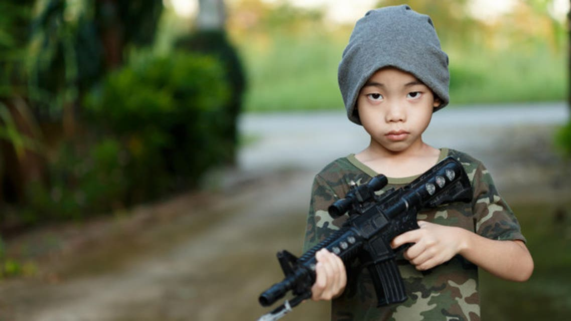 Stock image:  asian boy wearing military shirt , with toy gun