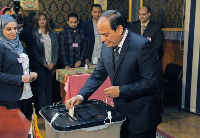 A handout picture released by the Egyptian Presidency on March 26, 2018 shows Egyptian President Abdel Fattah al-Sisi (C) casting his vote on the first day of the 2018 presidential elections at a polling station in the capital Cairo. (AFP)