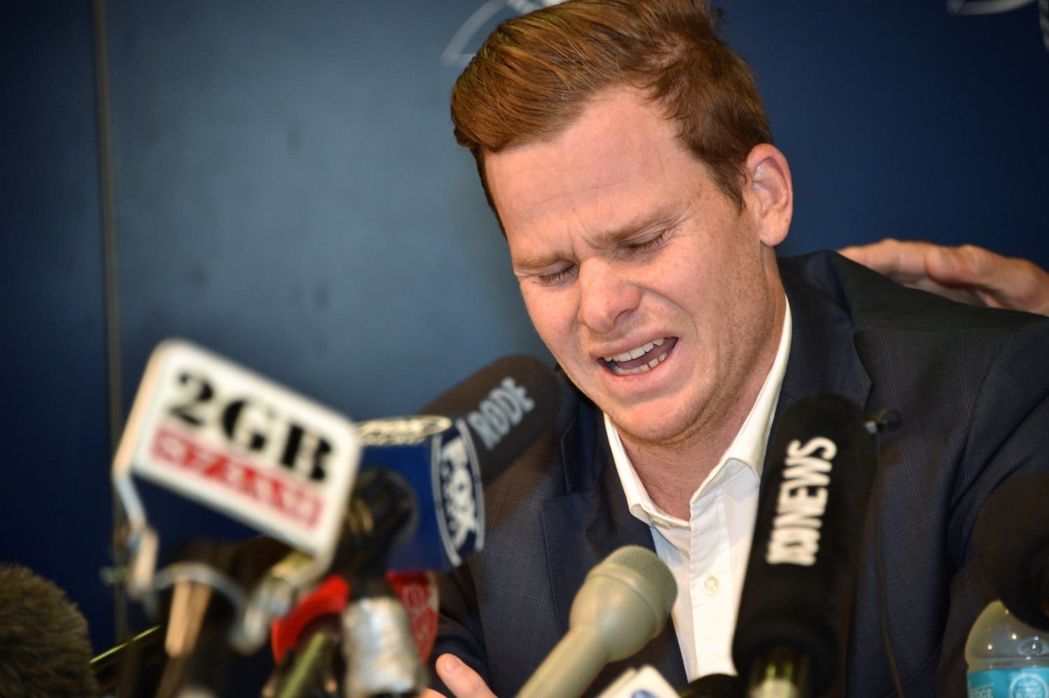 Cricketer Steve Smith reacts at a press conference at the airport in Sydney on March 29, 2018, after returning from South Africa. (AFP)
