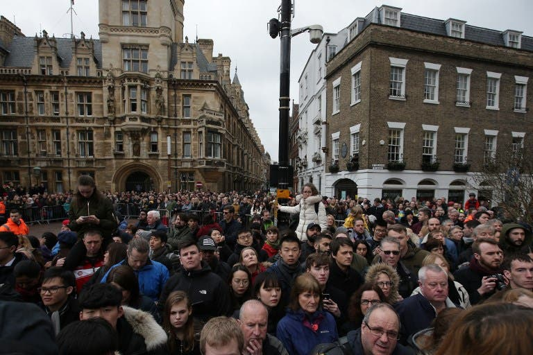 People wait for guests to arrive for the funeral of British scientist Stephen Hawking at the Church of St Mary the Great, in Cambridge on March 31, 2018. Friends, family and colleagues of British scientist Stephen Hawking gathered to pay their respects at his private funeral in Cambridge, where he spent most of his extraordinary life. Daniel LEAL-OLIVAS / AFP
