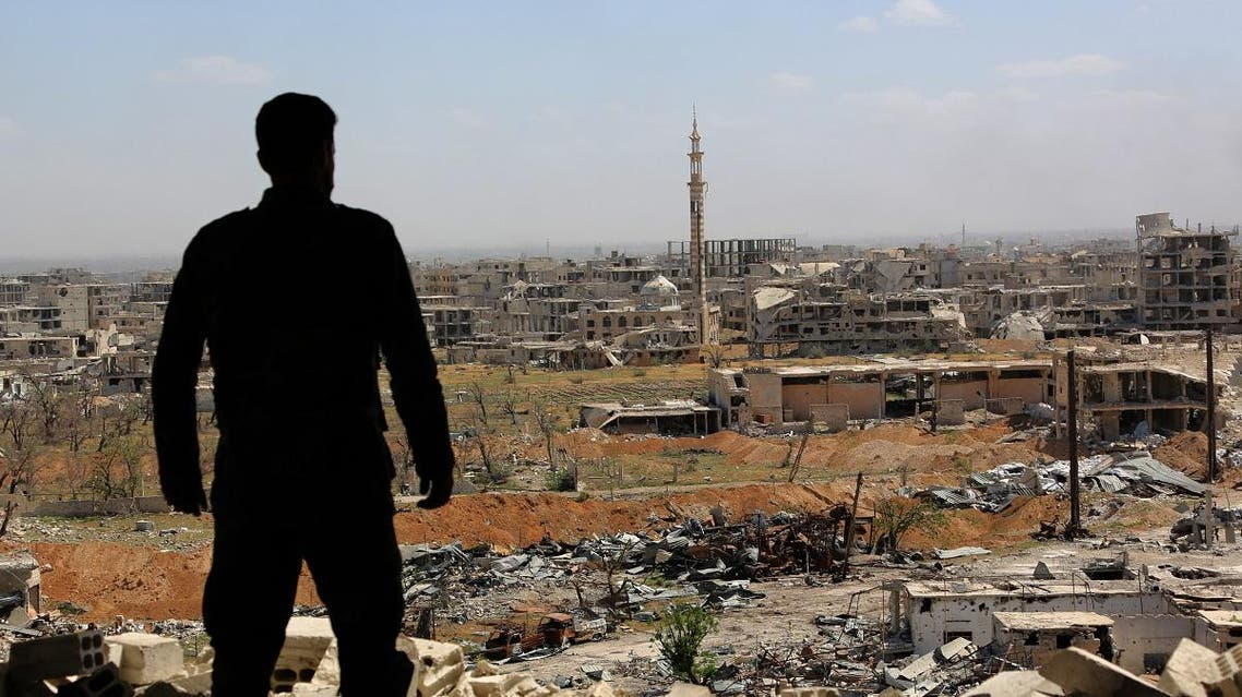 A Syrian soldier looks at destroyed buildings nearly a week after retaking the town of Harasta from the rebels, in Eastern Ghouta. (File photo: AFP)