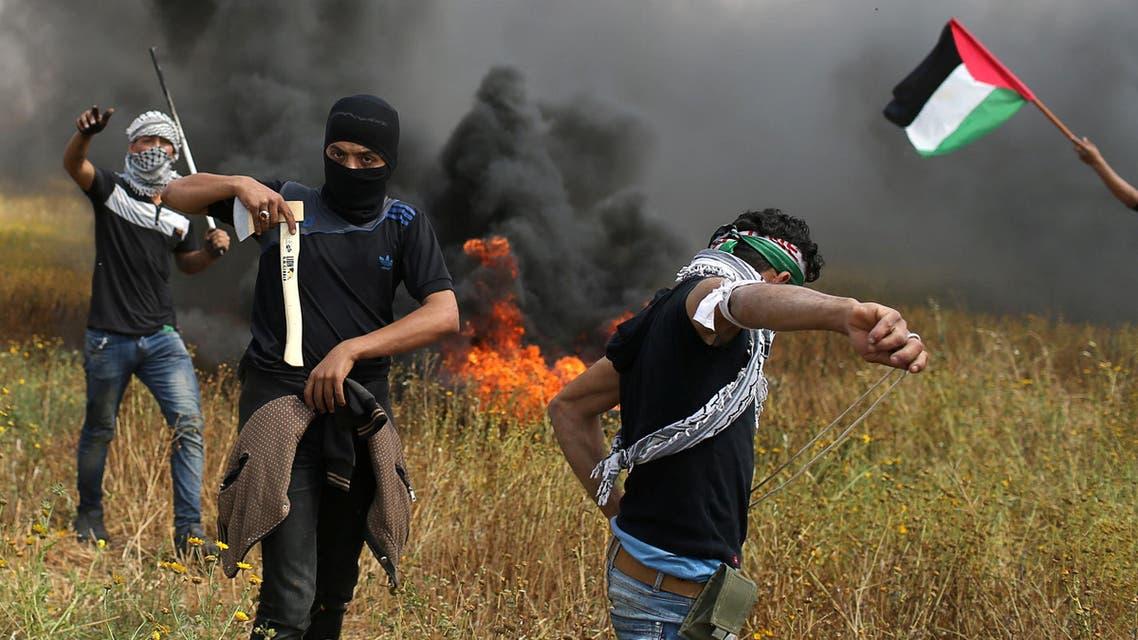 محتجون فلسطينيون أثناء اشتباكات مع الجيش الإسرائيلي على الحدود مع غزة الجمعة