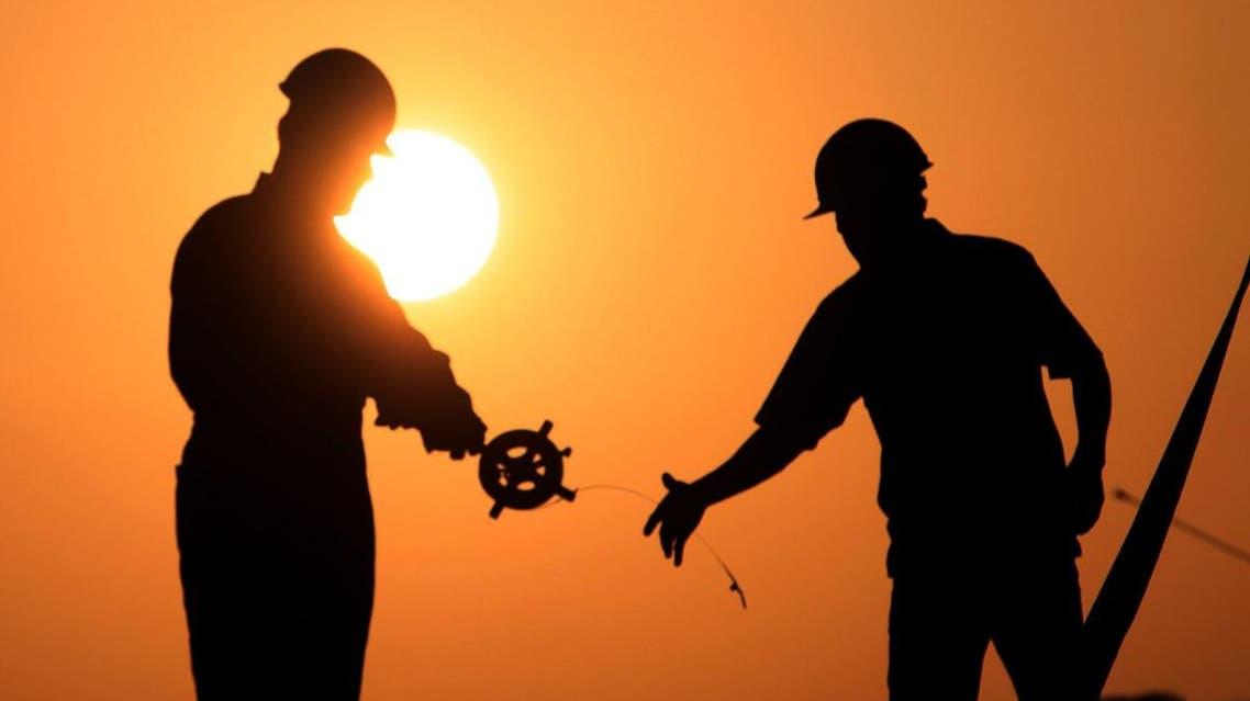 Oil men work on a new oil rig in the oil field of Sakhir, Bahrain. (File photo: AP)