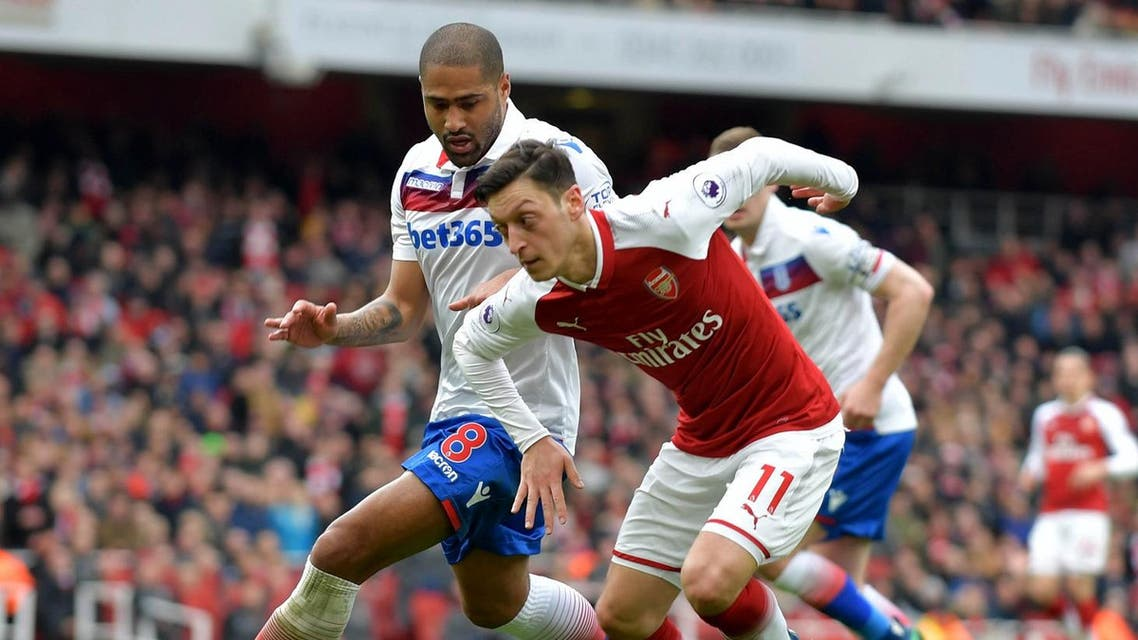 Arsenal's German midfielder Mesut Ozil (R) vies with Stoke City's English defender Glen Johnson during the English Premier League football match against Stoke City at the Emirates Stadium in London. (AFP)