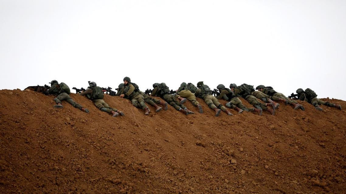 Israeli soldiers are seen next to the border fence on the Israeli side of the border with the northern Gaza Strip. (Reuters)