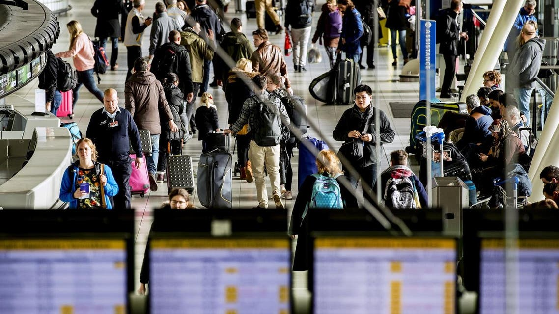 Passengers check plane departures timetables at Amsterdam's Schiphol airport. (AFP)