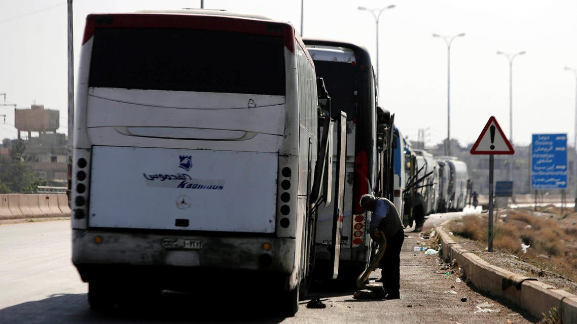 A driver stands next to a bus as he waits to cross into the town of Douma, eastern Ghouta, to evacuate rebels and their families, at Wafideen camp in Damascus, Syria April 1, 2018. REUTERS/Omar Sanadiki
