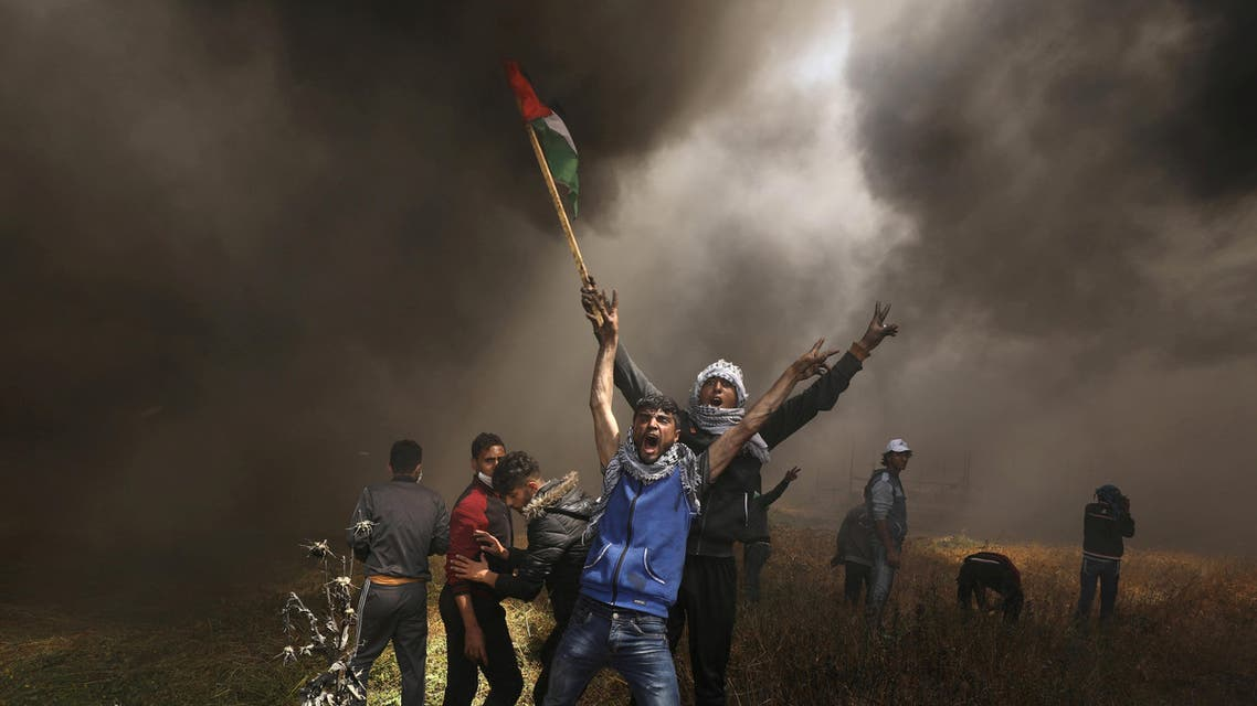 Palestinian demonstrators shout during clashes with Israeli troops at a protest demanding the right to return to their homeland, at the Israel-Gaza border east of Gaza City April 6, 2018. REUTERS/Mohammed Salem