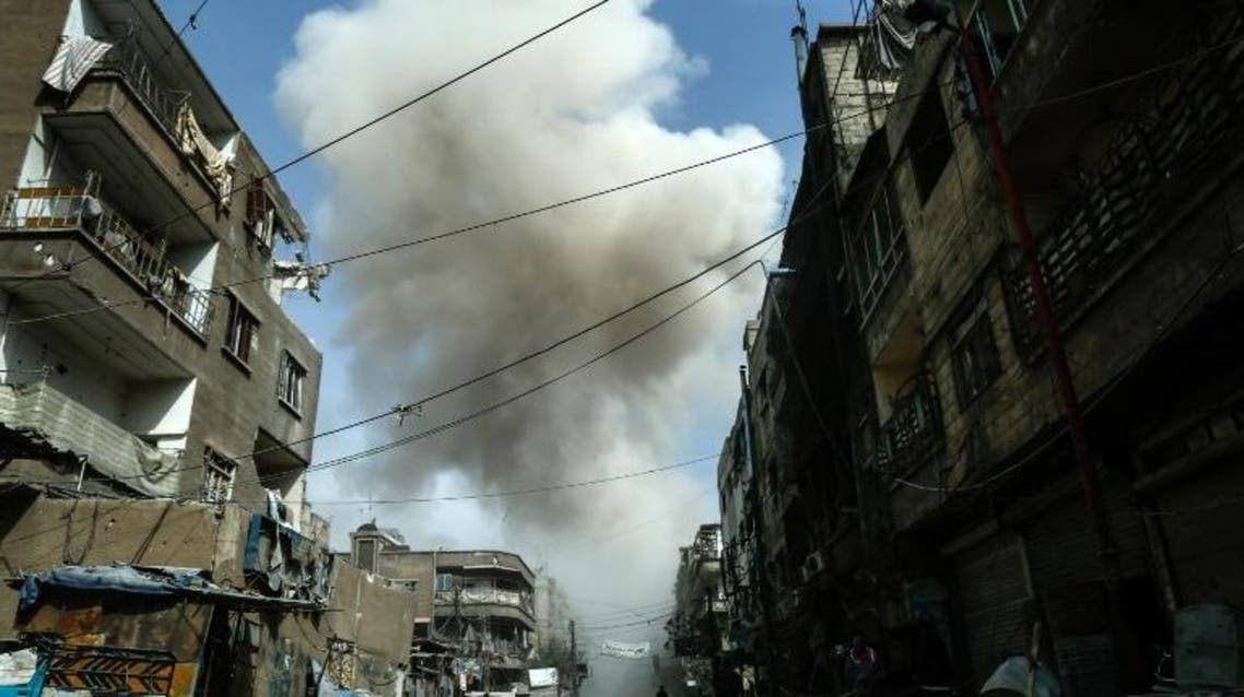 Smoke billows from buildings following a reported air strike on Douma, the main town of Syria's rebel enclave of Eastern Ghouta on March 20, 2018. HASAN MOHAMED / AFP