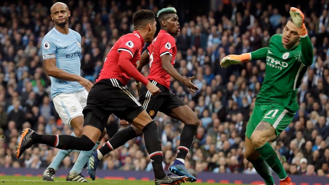 Manchester United's Chris Smalling celebrates with Paul Pogba, (center right), after scoring his side's third goal past Manchester City goalkeeper Ederson (right), during the English Premier League soccer match. (AP)