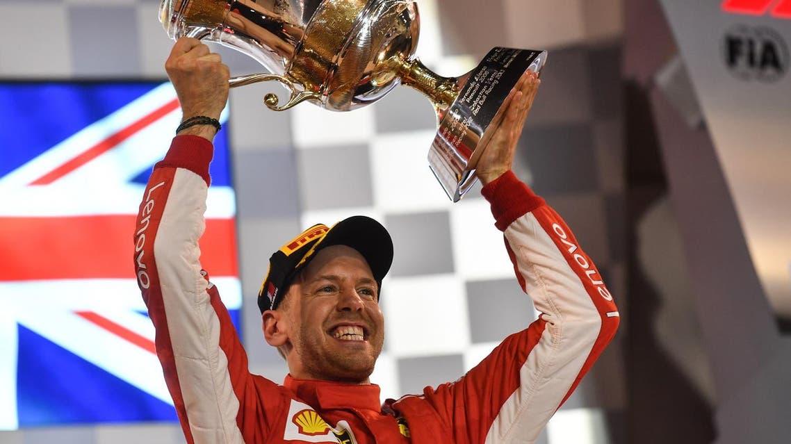 Ferrari's Sebastian Vettel raises his trophy on the podium after winning the Bahrain Formula One Grand Prix at the Sakhir circuit in Manama on April 8, 2018. (AFP)