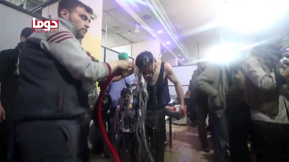 An image grab taken from a video released by the Douma City Coordination Committee shows unidentified volunteers spraying a man with water at a make-shift hospital following an alleged chemical attack on the rebel-held town of Douma on April 7, 2018.  HO / Douma City Coordination Committee / AFP