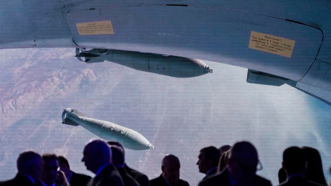 Participants of the Conference on International Security gather together near a big screen showing a Russian warplane unloading its weapons over target in Syria. (AP)