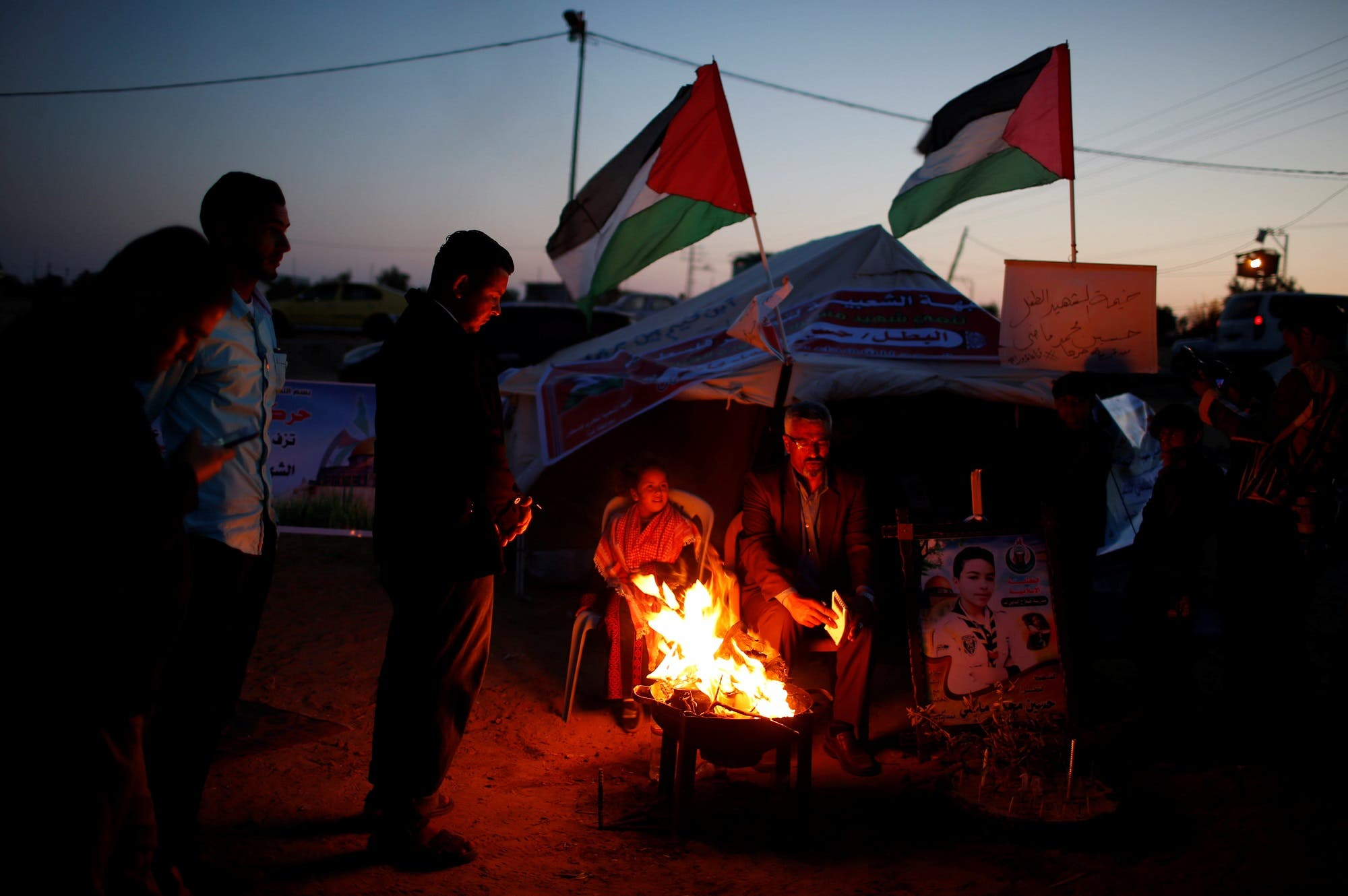 People participate in a symbolic birthday party for Hussein Madi at a tent city protest east of Gaza City on April 9, 2018. (Reuters)