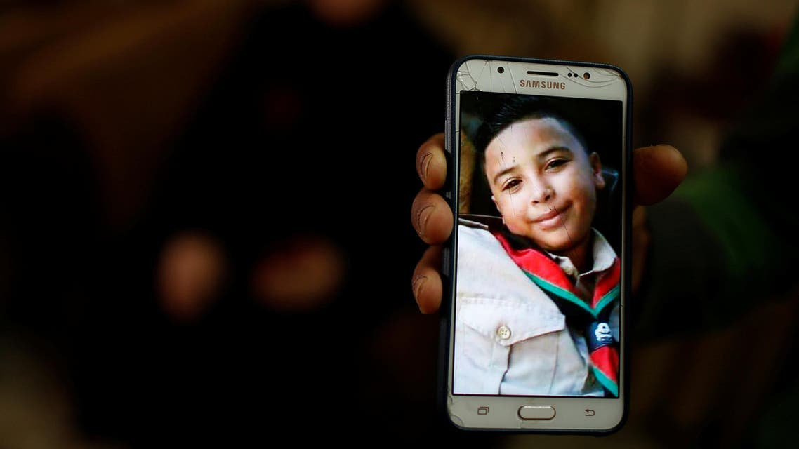 A relative holds a mobile phone showing the picture of Hussein Madi in Gaza City on April 9, 2018. (Reuters)