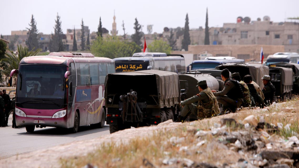 Buses carry rebels and their families who left Douma, at the entrance of the Wafideen camp in Damascus, Syria April 12, 2018. REUTERS/Omar Sanadiki