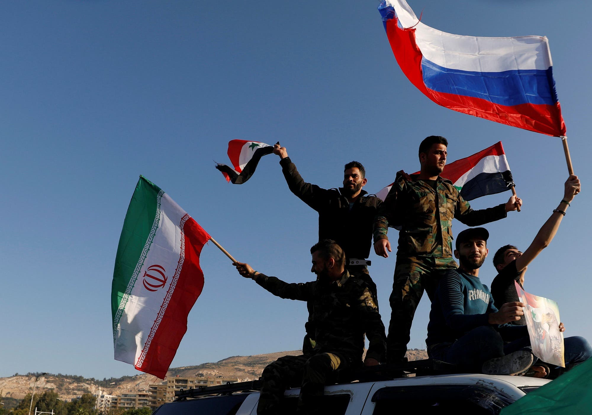 Syrians wave Iranian, Russian and Syrian flags during a protest against US-led air strikes in Damascus on April 14, 2018. (Reuters)