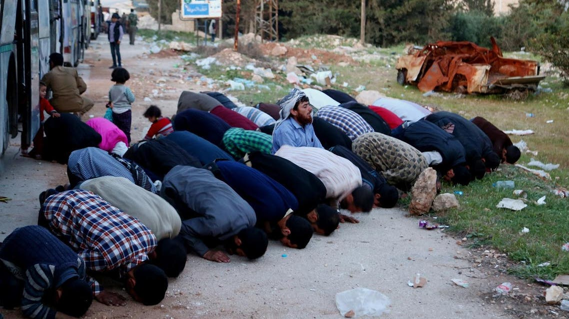 Syrian men pray as buses with Jaish al-Islam fighters and their families on board arrive from their former rebel bastion of Douma in Eastern Ghouta at the Abu al-Zindeen checkpoint,  on April 14, 2018. (AFP)