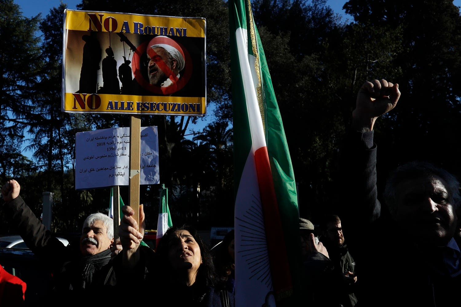 """An Iranian opposition group protester holds up a placard bearing a picture of Iran President Hassan Rouhani and writings reading """"No to Rouhani no to executions"""", during a protest outside the Iran Embassy, in Rome, on Jan. 2, 2018. (AP)"""