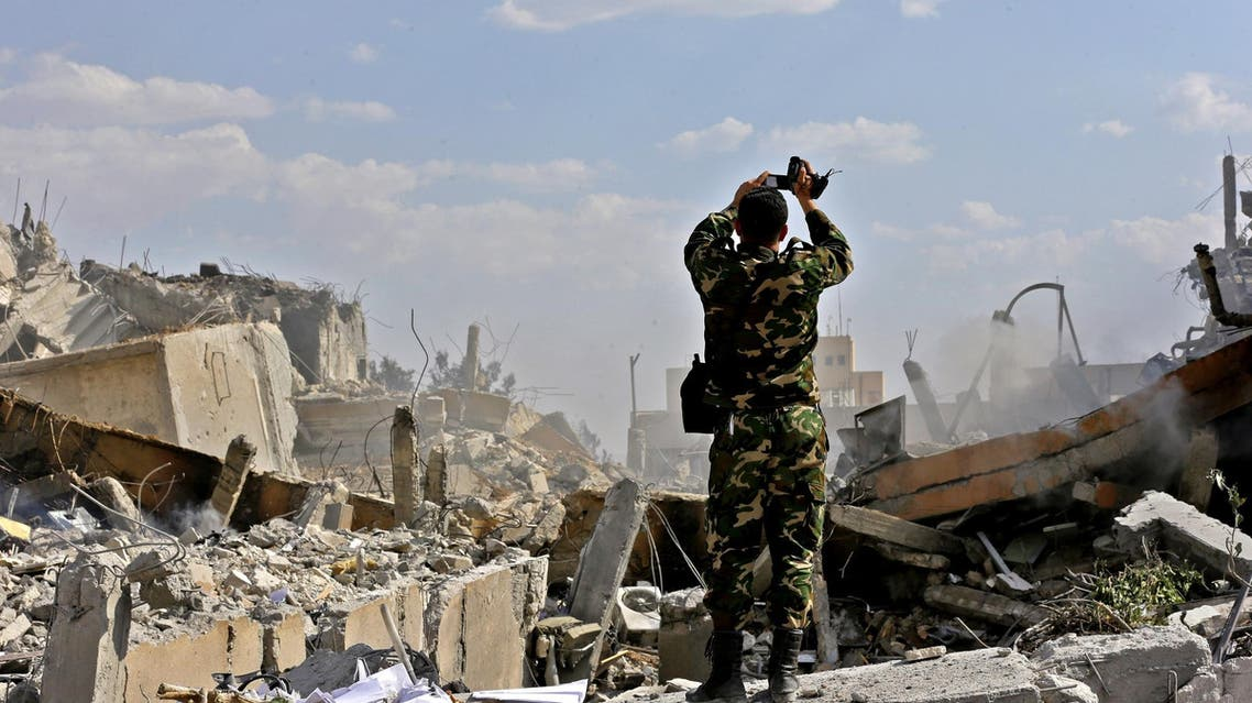 A Syrian soldier inspects the wreckage of a building in the Barzeh district, north of Damascus, on April 14, 2018. (AFP)