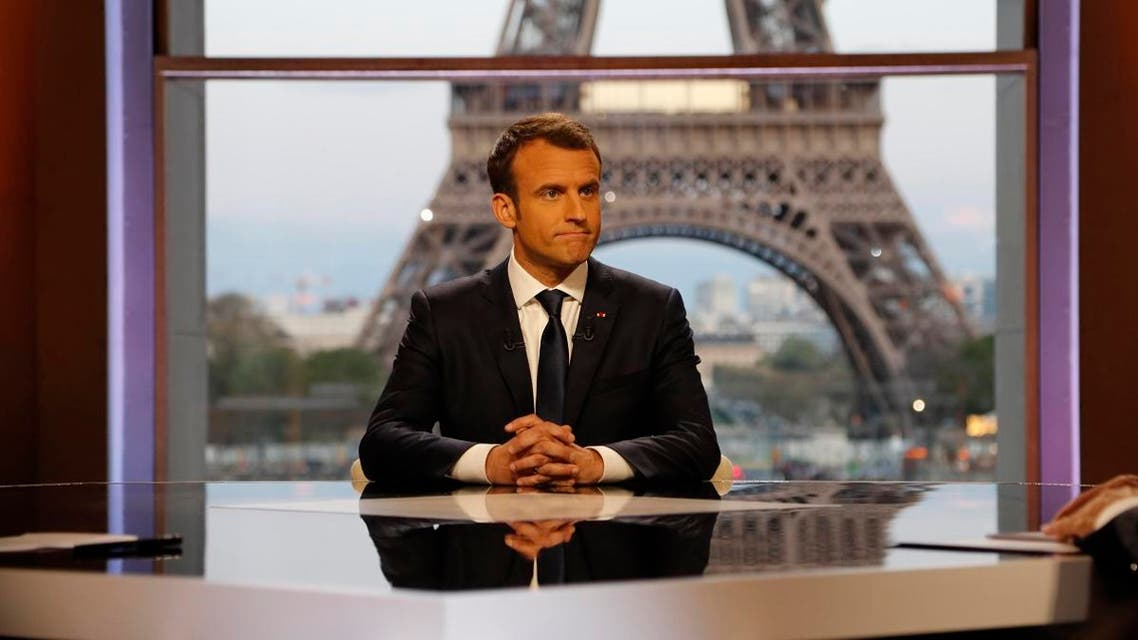 French President Emmanuel Macron poses on the TV set before an interview with RMC-BFM and Mediapart French journalists. (Reuters)