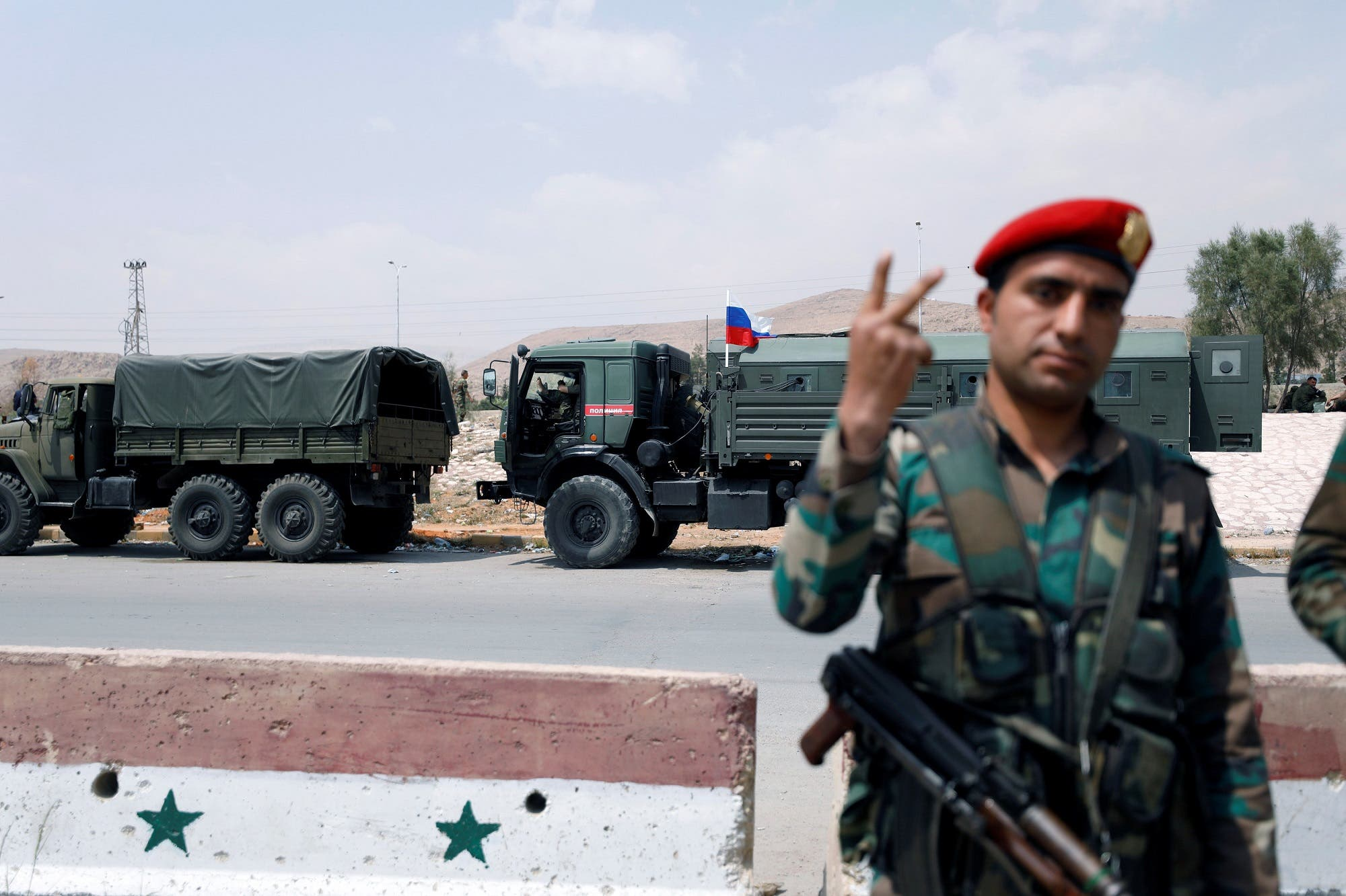 A Syrian Army solider gestures as a Russian flag is seen on a military vehicle, at the entrance of the Wafideen camp in Damascus on April 12, 2018. (Reuters)