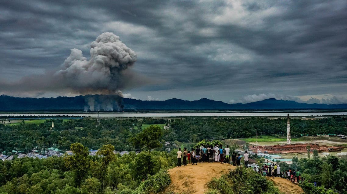 Third-placed image of World Press Photo 2018 contest for General News Singles taken by Md Masfiqur Akhtar Sohan shows a group of Rohingya watch as houses burn across the border in Myanmar on September 9, 2017. (Reuters)
