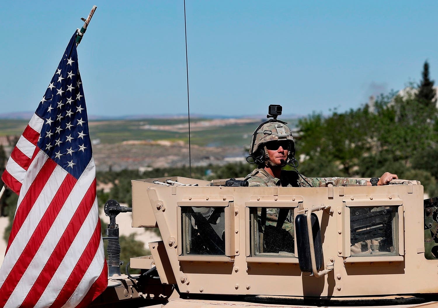 A US soldier sits on his armored vehicle on a road leading to Manbij, north Syria, on April 4, 2018. (AP)