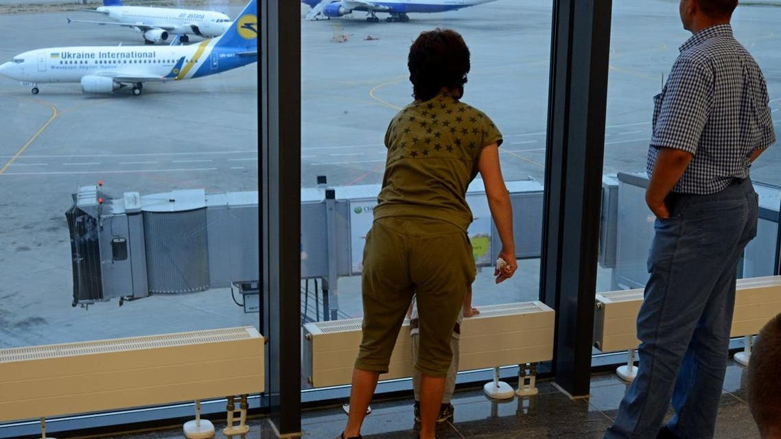 Passengers look in the window as they rest in the transit zone in Sheremetyevo airport terminal F in Moscow. (AFP)