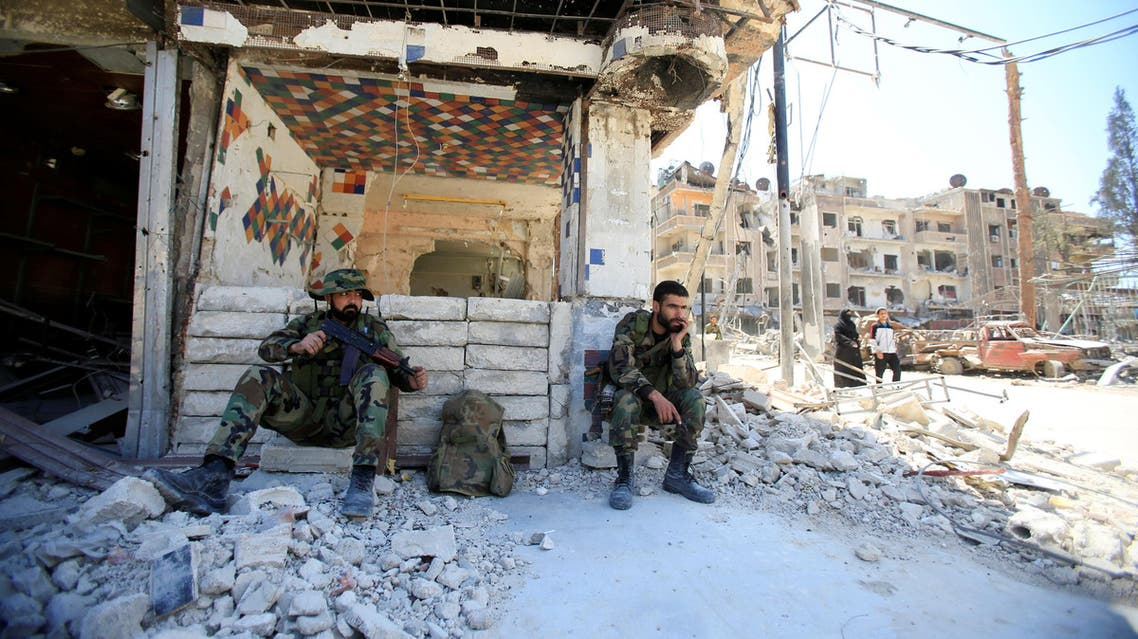 Members of Syrian police sit at a damaged building at the city of Douma, Damascus, Syria April 16, 2018. (Reuters)