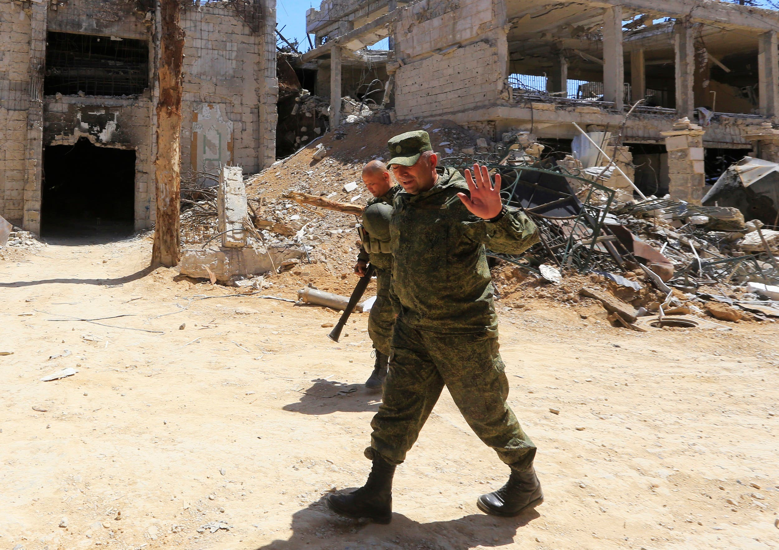 Russian forces walk past damaged buildings in Douma during an organized media tour on April 16, 2018. (AFP)