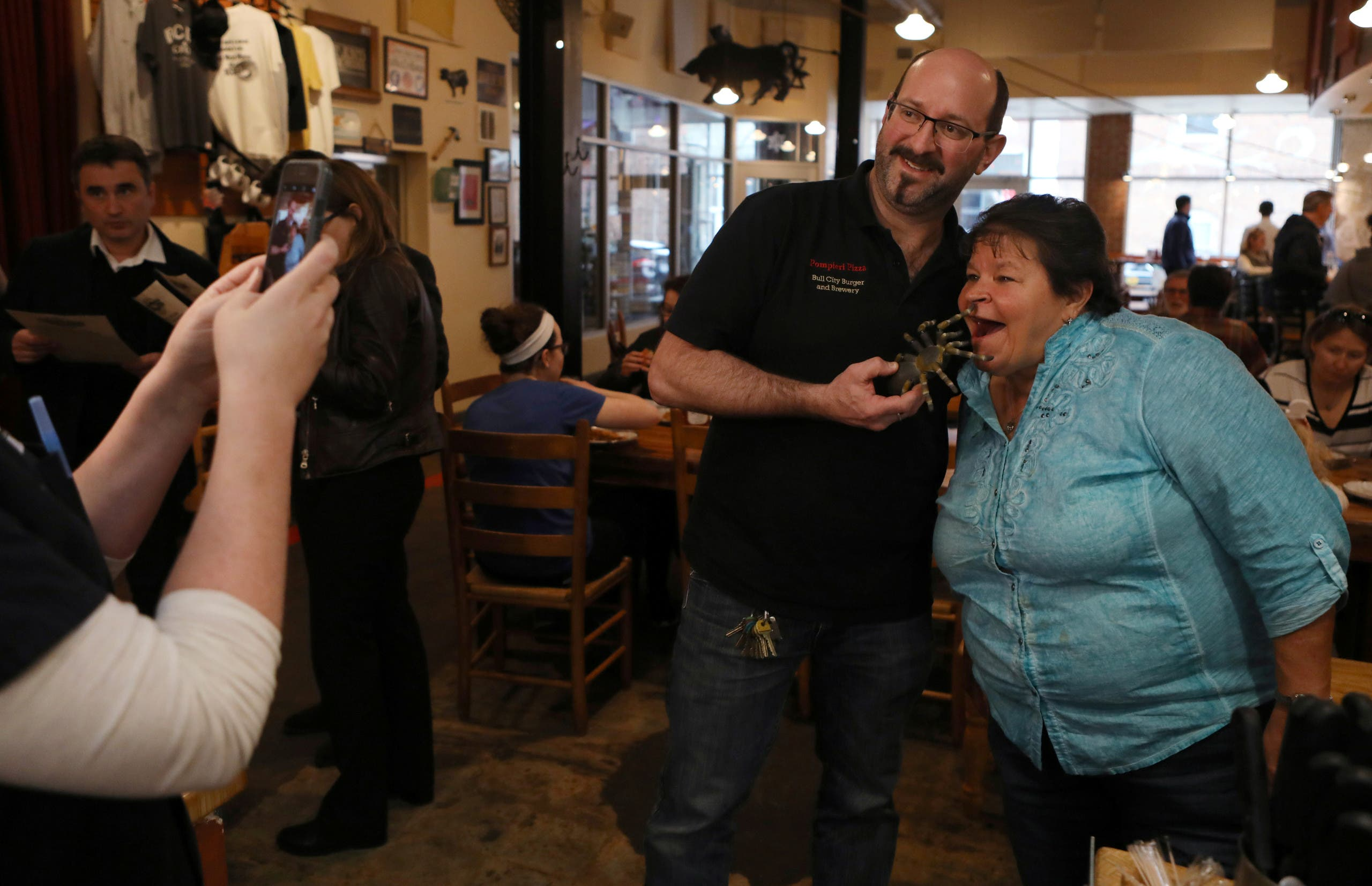 Bull City Burger and Brewery owner Seth Gross posses with a customer as he holds a tarantula toy before the restaurant serves their tarantula burger to another customer in celebration of Exotic Meat Month in Durham, North Carolina, U.S. April 16, 2018. Picture taken April 16, 2018. REUTERS/Jim Urquhart