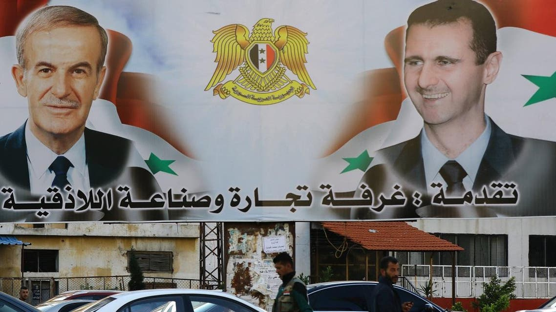 A billboard sponsored by Latakia's chamber of commerce and industry shows pictures of Syrian President Bashar al-Assad (R) and his late father former president Hafez al-Assad in the coastal city of Latakia. (AFP)