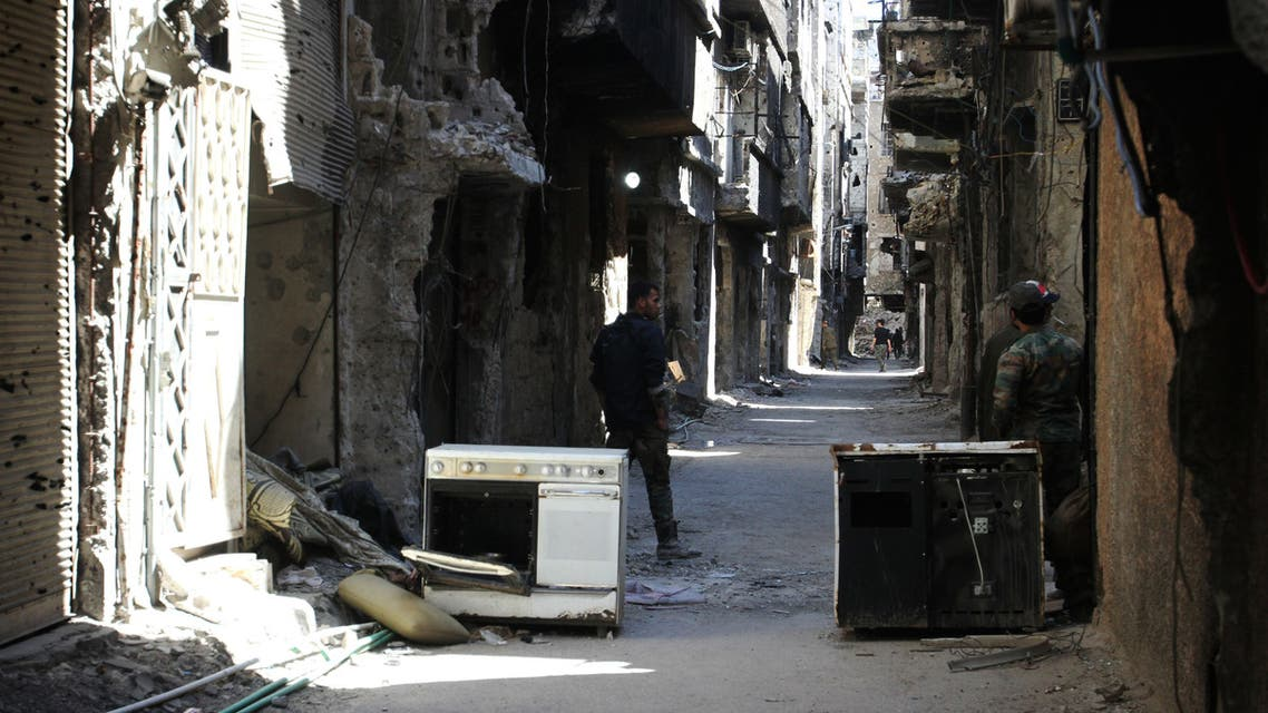 Men stand in an alleyway of demolished buildings in the Yarmuk Palestinian refugee camp in the Syrian capital Damascus on April 6, 2015. Around 2,000 people have been evacuated from the camp after the Islamic State group seized large parts of it. At least 26 people, including civilians as well as fighters from IS and Palestinian factions, had been killed in the camp according to the Syrian Observatory for Human Rights. AFP PHOTO / YOUSSEF KARWASHAN  YOUSSEF KARWASHAN / AFP