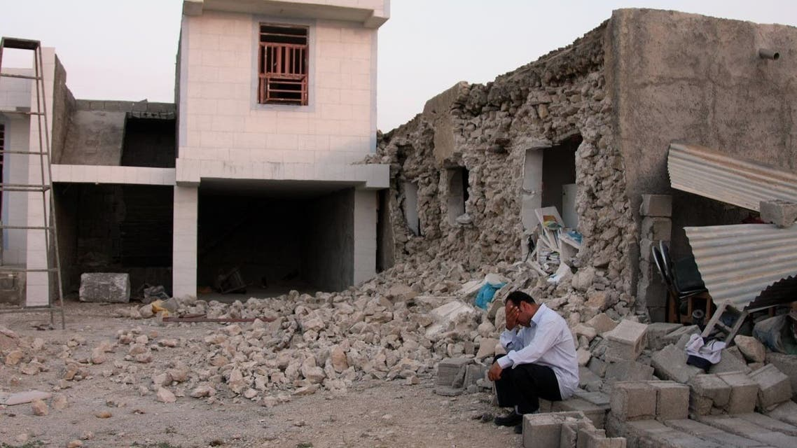 An Iranian man squats next to his destroyed house in the town of Shonbeh, southeast of Bushehr, on April 9, 2013 after a powerful earthquake struck near the Gulf port city of Bushehr. The 6.1 magnitude quake killed at least 30 people and injured 800 but Iran's only nuclear power plant was left intact, officials said. AFP PHOTO/FARS NEWS/MOHAMMAD FATEMI